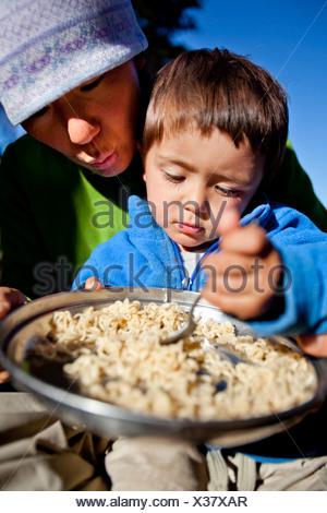 Un garçon est assis sur les genoux de sa mère pendant qu'ils mangent les nouilles dans l'arrière-pays. Ils sont campés à Squaw Pass. Banque D'Images