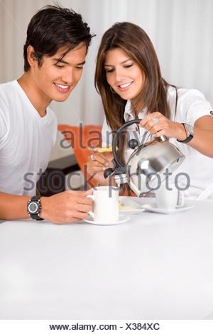 Jeune couple ayant le petit déjeuner à la maison à la recherche heureux Banque D'Images