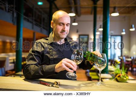 Vin blanc Waiter pouring into glass Banque D'Images