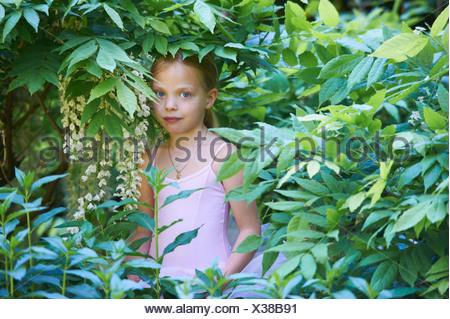 Fille en costume de ballet se cachant dans bush Banque D'Images