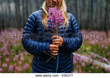 Portrait of mid adult woman holding manteau rembourré fleurs sauvages, le lac Moraine, Banff National Park, Alberta Canada