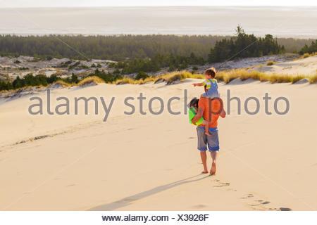 Père transportant des enfants (2 à 3 ) sur la plage Banque D'Images