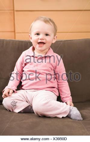 Baby Girl 18 mois assis sur le canapé en riant Banque D'Images