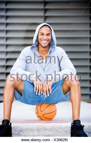 Portrait of a smiling young African American man dans un haut à capuchon gris assis sur un terrain de basket-ball. Banque D'Images
