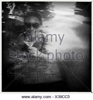 Woman drinking cocktail in swimming pool Banque D'Images