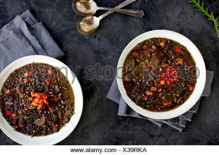 Lentilles Soupe Coco sésame noir. Photographié sur un fond gris foncé/noir. Banque D'Images