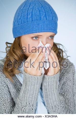 Une jeune femme s'être mouché le nez Banque D'Images