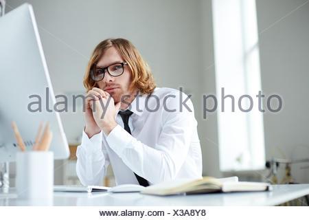 Portrait d'un bel homme dans la soirée à l'ordinateur Banque D'Images