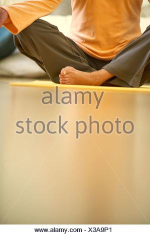 Une femme assise, les jambes croisées sur un tapis de yoga, close-up Banque D'Images