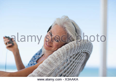 Senior woman listening to music on mp3 player Banque D'Images