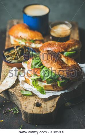 Le petit-déjeuner avec des bagels avec du saumon, avocat, fromage, crème, basilic, câpres, café expresso sur planche de bois rustique sur fond sombre, selective focus. Banque D'Images