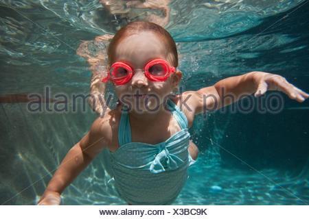 Underwater portrait of girl apprendre à nager et smiling at camera Banque D'Images