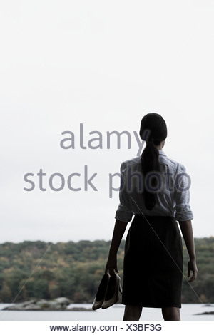 Une businesswoman holding high heeled shoes Banque D'Images
