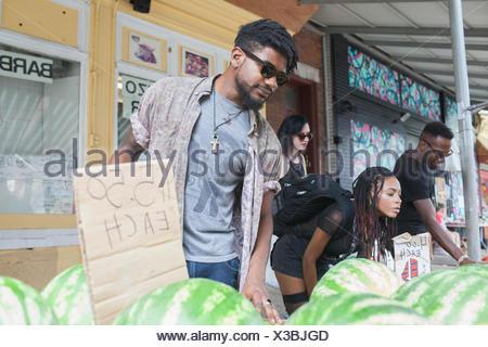 Un jeune homme et de la femme à un étal de fruits. Banque D'Images