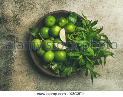 Flatlay fraîchement cueillies de limes et de feuilles de menthe bio pour faire des cocktails et de la limonade en plaque en bois sur fond noir en béton gris, vue du dessus Banque D'Images