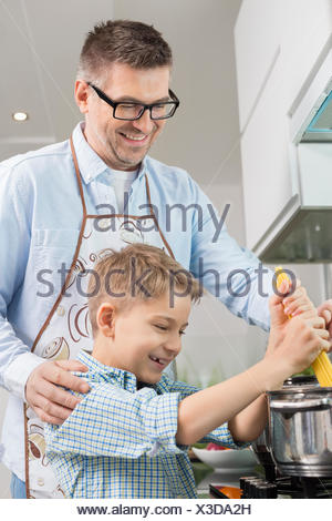 Heureux père et fils spaghetti préparation together in kitchen Banque D'Images
