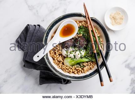 Le miso Ramen nouilles asiatiques avec shiitake, le tofu et le chou pak-choï dans un bol sur fond de marbre blanc Banque D'Images