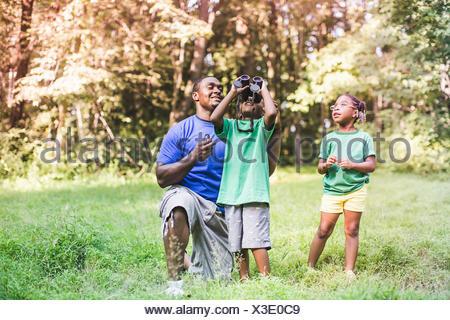 Le père avec son fils et sa fille l'observation des oiseaux en eco forest camp Banque D'Images