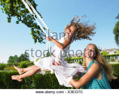 Jeune fille sur une balançoire, poussée par sa soeur Banque D'Images