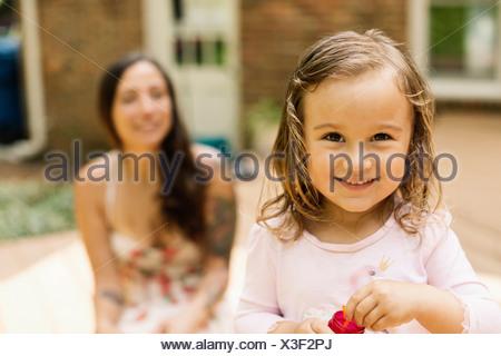 Portrait of female toddler avec mère blowing bubbles in garden Banque D'Images