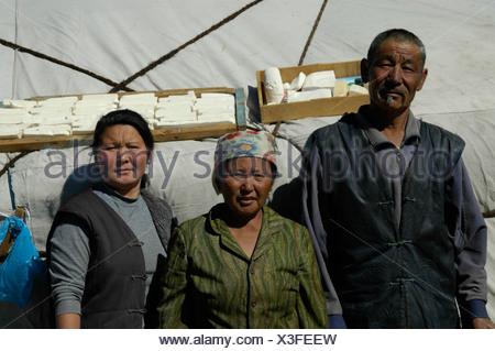 Nomads homme et deux femmes sont debout devant leur yurte de fromage est le séchage sur le toit près de l'Altaï mongol Kharkhiraa Banque D'Images