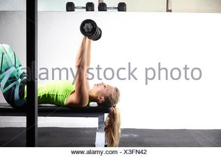 Jeune femme couché sur banc de musculation en salle de sport de la barre de levage de Bell Banque D'Images