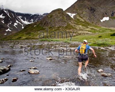 Trail Runner éclabousse par Middle Fork Creek Campbell lors de l'exécution de Mont Elliot à Wolverine Peak de Rusty Point, Alaska Banque D'Images