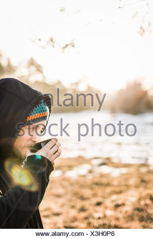 Portrait of young man drinking coffee at lakeside Banque D'Images
