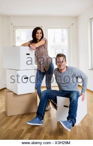 Toute la longueur du couple avec des cartons à la maison Banque D'Images