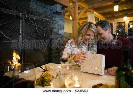 Man giving woman gift à fireside restaurant table Banque D'Images