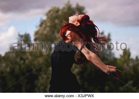 Portrait de femme à tête rouge sautant en plein air