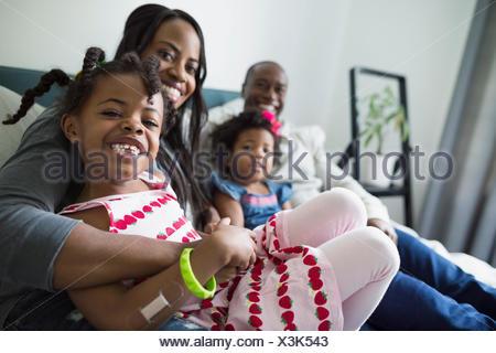 Portrait smiling young family dans la chambre Banque D'Images