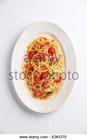 Spaghetti à la sauce tomate, tomates confites et parmesan sur fond blanc Banque D'Images