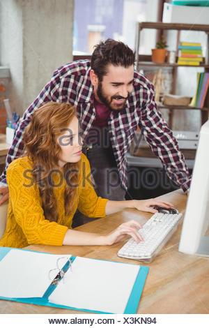 La femme et l'homme à at computer in office Banque D'Images