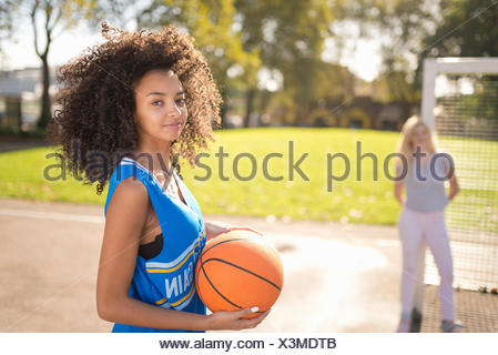Portrait of young woman holding basketball Banque D'Images