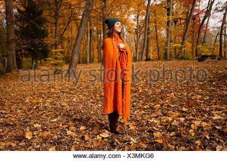Jeune femme enveloppée dans une couverture orange en forêt Banque D'Images