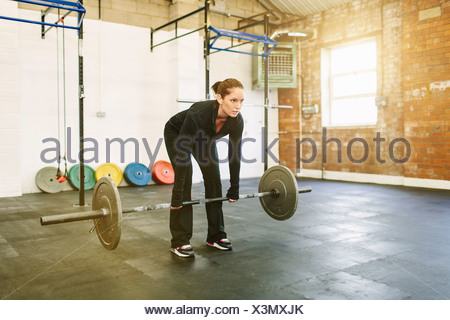 Woman lifting barbell in gym Banque D'Images