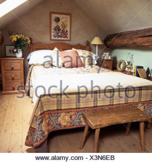 Vieux banc de bois ci-dessous lit avec lit à motifs et jeter la crème couvrir dans une chambre mansardée avec parquet Banque D'Images