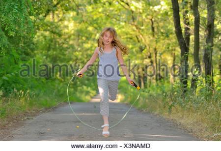 Petite fille saute par-dessus la corde dans la forêt. Banque D'Images
