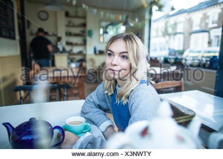 Jeune femme assise dans un café, à la fenêtre de