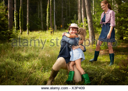 Un homme serrant un jeune enfant. Une famille sur un bois à pied. Banque D'Images