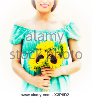 Young woman holding sunflowers Banque D'Images