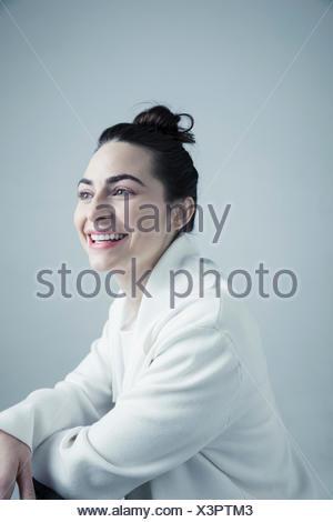 Portrait of smiling Caucasian brunette jeune femme en blanc pour homme à l'écart avec cheveux bun Banque D'Images