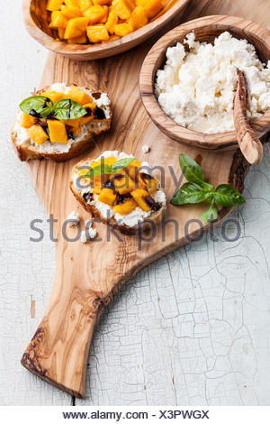 Bruschetta à la mangue hachée, le basilic et le fromage de chèvre sur la baguette fraîche Banque D'Images