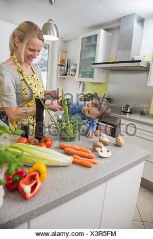 Garçon regardant sa mère alors qu'elle saveurs salade, smiling Banque D'Images