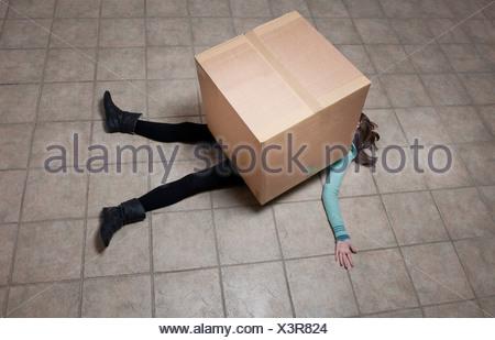 Teenage girl lying sous boîte carton Banque D'Images
