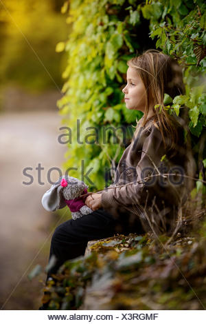 Vue latérale d'une jeune fille tenant un lapin en peluche jouet Banque D'Images