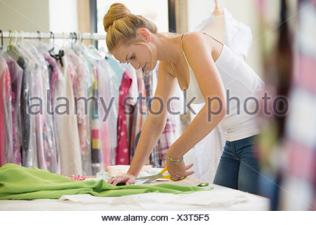 Fashion Designer Cutting Out Pattern dans Fabric In Studio Banque D'Images