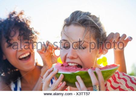 Young woman eating watermelon comme ami tire ses oreilles Banque D'Images
