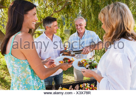Adult Family Group Cooking Barbeque In Countryside Banque D'Images